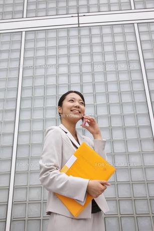 ビルの前でファイルを片手に携帯で電話をするビジネスウーマンの素材 [FYI00119178]
