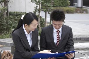 ファイルを持ち笑顔で話すビジネスマンとビジネスウーマンの素材 [FYI00119181]