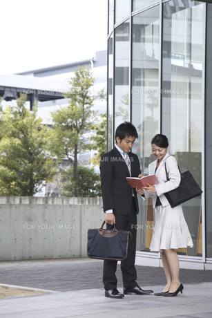 ビルの前でスケジュールを確認する会社員の素材 [FYI00119187]