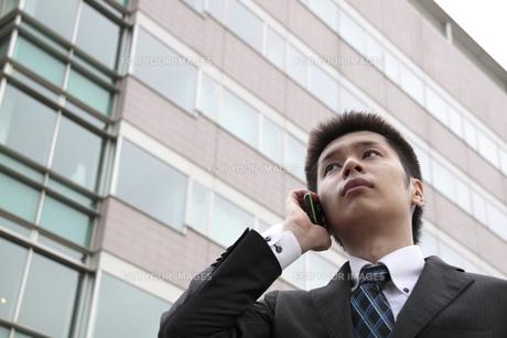 ビルの前で電話をする若いビジネスマンの写真素材 [FYI00119198]