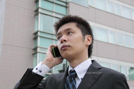 ビルの前で電話をしている若いビジネスマンの写真素材 [FYI00119206]