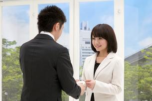 名刺交換をするビジネスマンと笑顔のビジネスウーマンの素材 [FYI00119208]