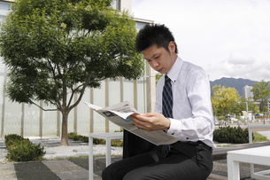 屋外で新聞を読む若いビジネスマンの素材 [FYI00119217]