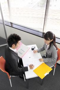 テーブルでミーティングをするビジネスマンとビジネスウーマンの素材 [FYI00119224]