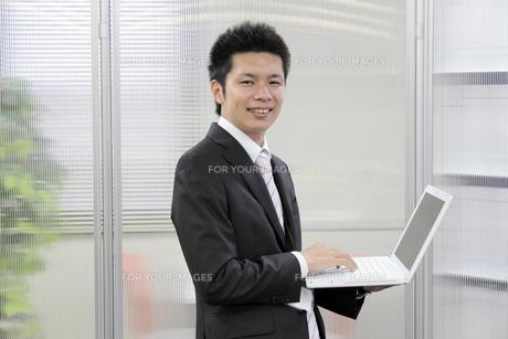ノートパソコンを持ち笑顔で立つビジネスマンの素材 [FYI00119229]