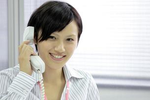 笑顔で電話をする若いビジネスウーマンの写真素材 [FYI00119243]