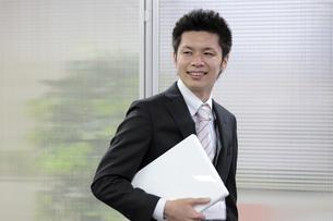 ノートパソコンを抱える若いビジネスマンの素材 [FYI00119248]