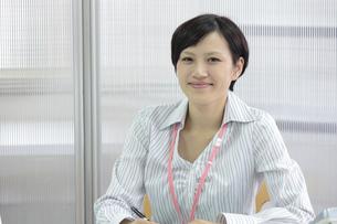 オフィスでにっこり微笑むビジネスウーマンの素材 [FYI00119250]