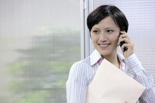 封筒を抱え電話をかけるビジネスウーマンの素材 [FYI00119251]