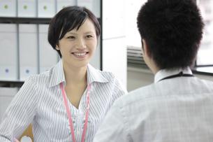 笑顔で上司と話すビジネスウーマンの素材 [FYI00119263]