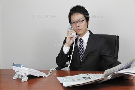 英字新聞を片手に電話をかけるビジネスマンの写真素材 [FYI00119265]