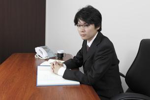 手を組み腰をおろすビジネスマンの写真素材 [FYI00119273]