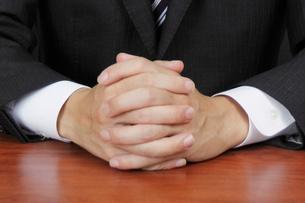 机の上で組まれた男性の手の写真素材 [FYI00119285]