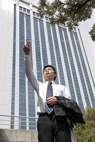 ビルの前で遠くを指さす若いビジネスマンの素材 [FYI00119287]