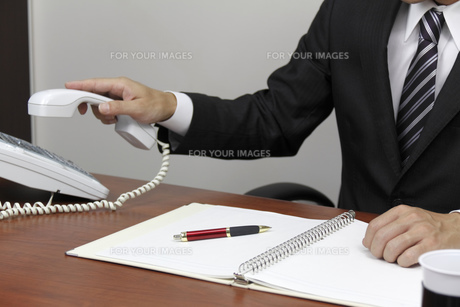 電話をとるビジネスマンの手元の写真素材 [FYI00119293]