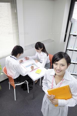 オフィス風景 笑顔で立つビジネスウーマンの素材 [FYI00119394]