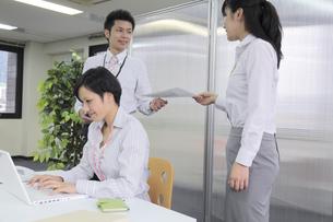 オフィス風景 上司に書類を渡すビジネスウーマンの素材 [FYI00119401]