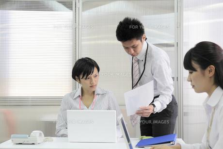 オフィス風景 書類を見つめるビジネスマンとビジネスウーマンの写真素材 [FYI00119415]