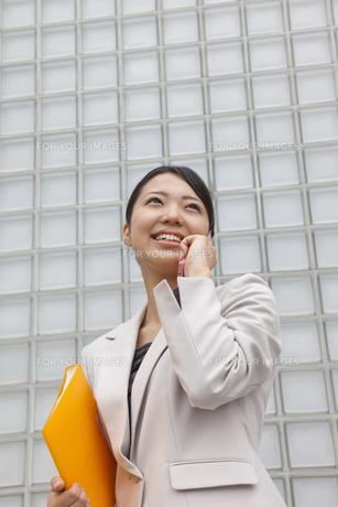オフィス街 携帯電話で話すビジネスウーマンの素材 [FYI00119418]