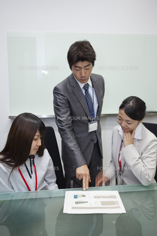 資料を見ながら打ち合わせをする上司と部下の写真素材 [FYI00119419]