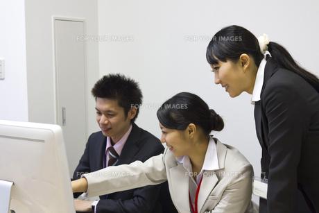 パソコンを見つめ話し合いをするビジネスチームの素材 [FYI00119430]