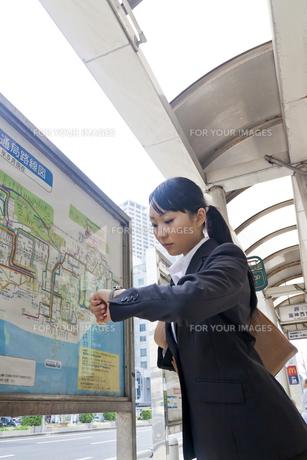 屋外 時間を確認するビジネスウーマンの写真素材 [FYI00119432]