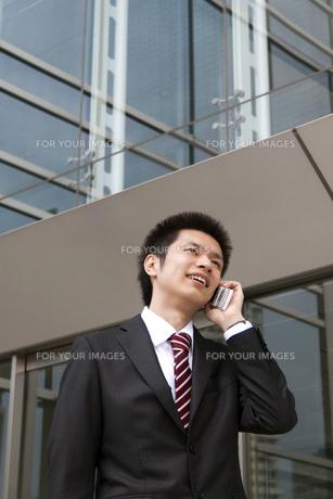 オフィス街で電話をする営業マンの写真素材 [FYI00119435]