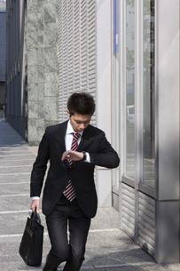 時間を気にしながら歩くビジネスマンの素材 [FYI00119437]