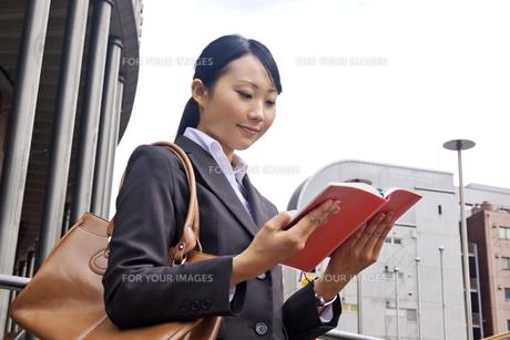 屋外 手帳を確認するビジネスウーマンの素材 [FYI00119448]