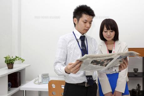 真剣に新聞を見つめるビジネスマンとビジネスうー麺の素材 [FYI00119459]