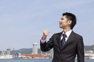 青空の下ガッツポーズをする男性の横顔の素材 [FYI00119513]