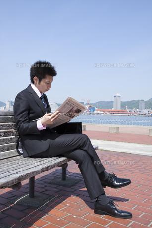 青空の下ベンチで親聞を読むビジネスマンの素材 [FYI00119526]