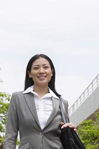 笑顔で屋外を歩くビジネスウーマンの素材 [FYI00119529]
