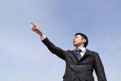 青空の下で遠くを指さすビジネスマンの素材 [FYI00119534]