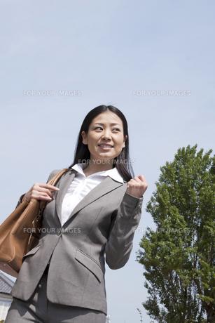 青空の下でガッツポーズをするビジネスウーマンの素材 [FYI00119538]