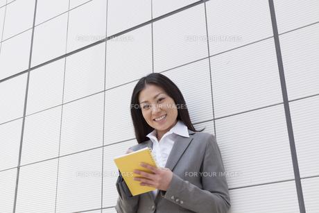 笑顔でメモを取るビジネスウーマンの素材 [FYI00119539]