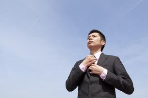 青空の下ネクタイを締めるビジネスマンの素材 [FYI00119540]