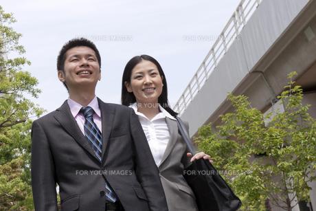 屋外を並んで歩くビジネスマンとビジネスウーマンの素材 [FYI00119543]