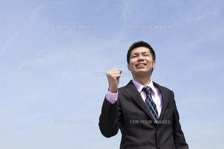 青空の下ガッツポーズをする笑顔のビジネスマンの素材 [FYI00119545]