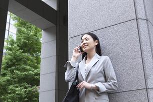 オフィス街で通話をしているビジネスウーマンの素材 [FYI00119548]