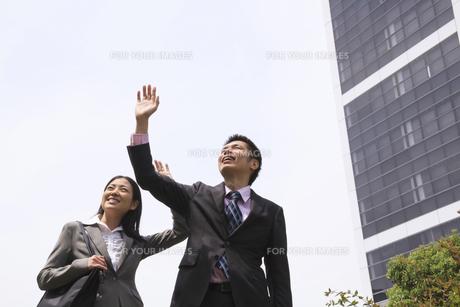 空に手をかざすビジネスマンとビジネスウーマンの素材 [FYI00119549]