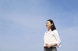 青空の下書類を抱える笑顔のビジネスウーマンの素材 [FYI00119553]