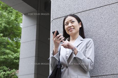 スマートフォンを操作するビジネスウーマンの素材 [FYI00119555]