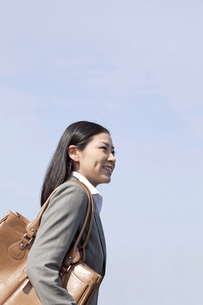 屋外を歩く笑顔のビジネスウーマンの素材 [FYI00119556]