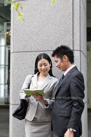 手帳を手に話し込むビジネスマンとビジネスウーマンの素材 [FYI00119557]