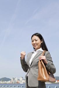 青空の下でガッツポーズをする若いビジネスウーマンの素材 [FYI00119559]