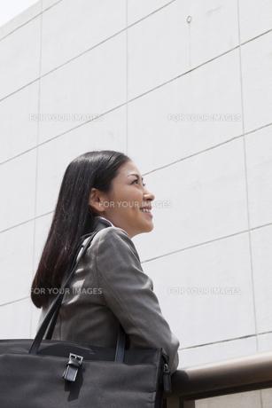 笑顔で遠くを見つめるビジネスウーマンの素材 [FYI00119561]