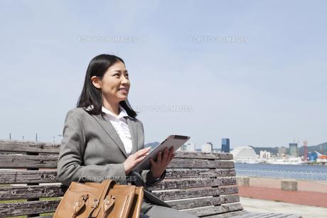 ベンチに座りiPadを操作するビジネスウーマンの素材 [FYI00119563]