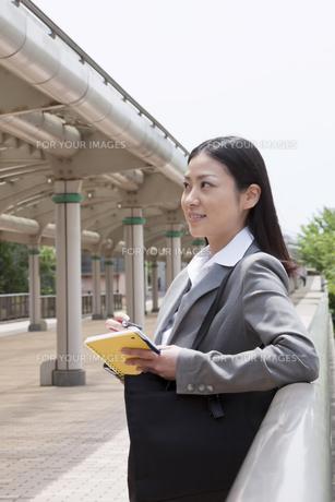 メモ帳を手に考え込むビジネスウーマンの素材 [FYI00119564]