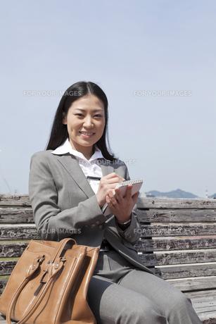 屋外でメモをとる若いビジネスウーマンの素材 [FYI00119567]
